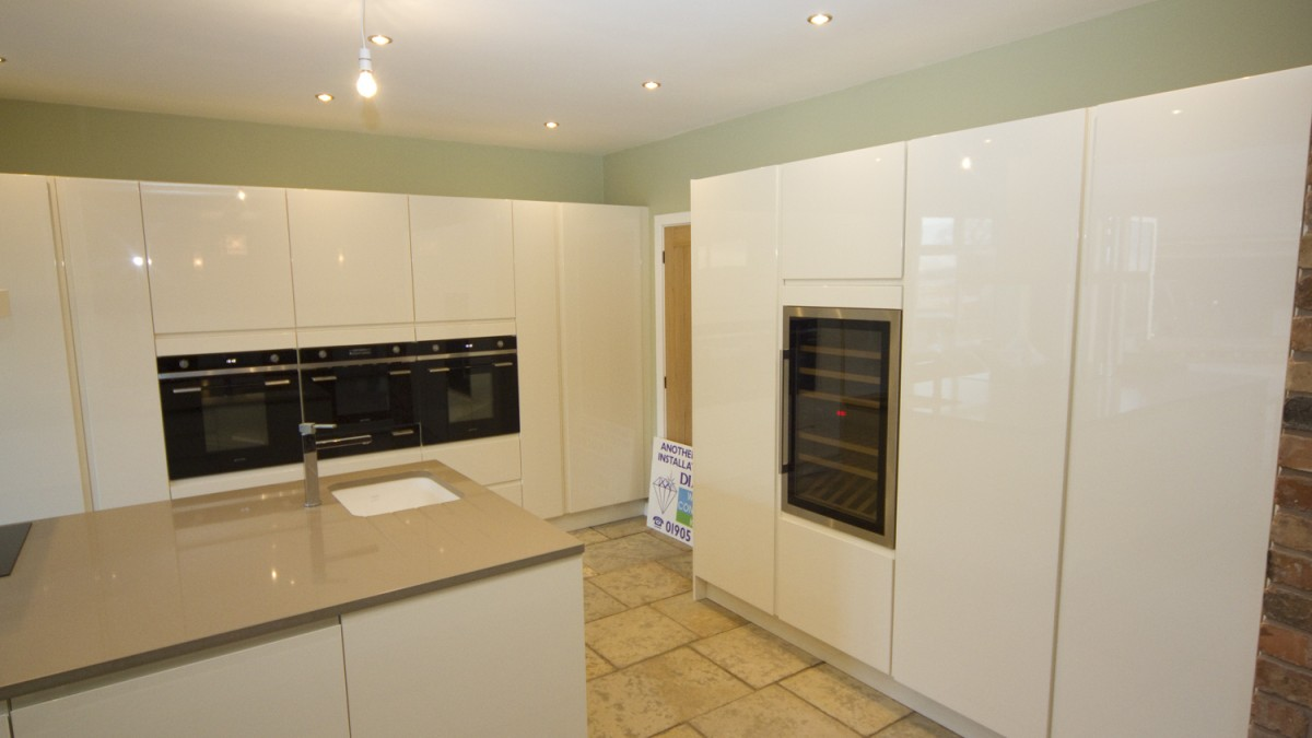 White Contemporary Cupboards With Glossy Finish And Grey Marble Worktops